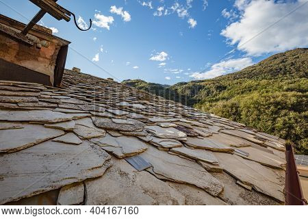 View Of The Old-fashioned Made Stone Roof Of Building In Abandoned Mountain Village With A Few Remai