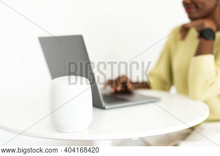 Smart speaker next to laptop with a woman