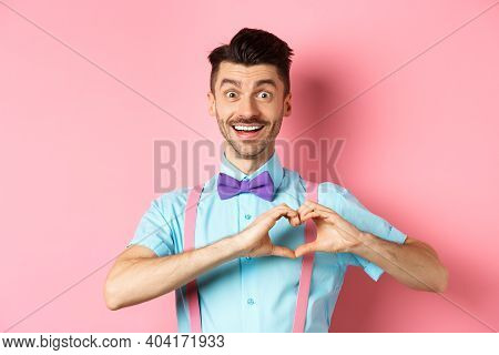 Passionate Guy In Funny Bow Tie Saying I Love You, Showing Heart Gesture On Valentines Day And Smili