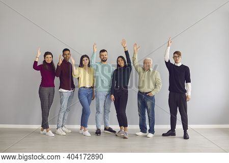 Group Of Happy Multiracial People Raising Their Hands Voting For A Good Suggestion