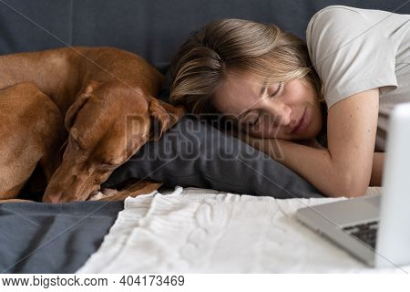 Woman With Her Lovely Dog Vizsla Sleeping Together On The Same Pillow On The Couch At Home, Napping