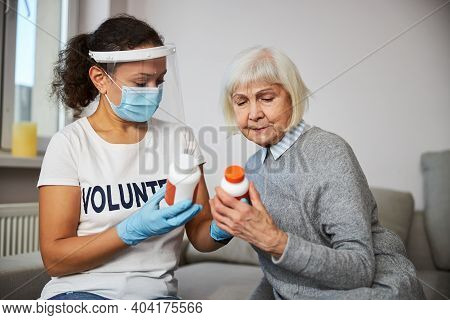 Aging Woman And Caretaker Reading The Pills Instructions