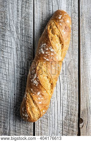 Crispy fresh baguettes on wooden table. Top view.