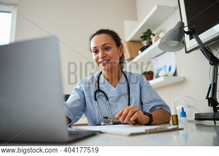 Doctor Clicking On A Laptop Before Her