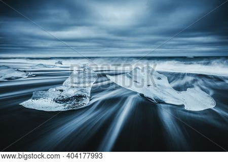 Majestic pieces of the iceberg sparkle on black sand. Location place Jokulsarlon lagoon, Vatnajokull national park, Iceland, Europe. Image of world landmarks. Art photo. Discover the beauty of earth.