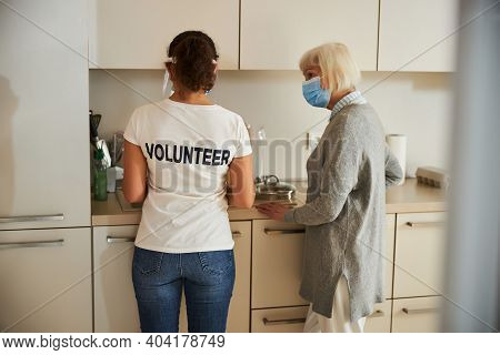 Caretaker Helping An Aged Lady With Chores