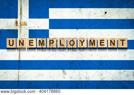 Unemployment. The Inscription On Wooden Blocks On The Background Of The Greece Flag. Unemployment Gr