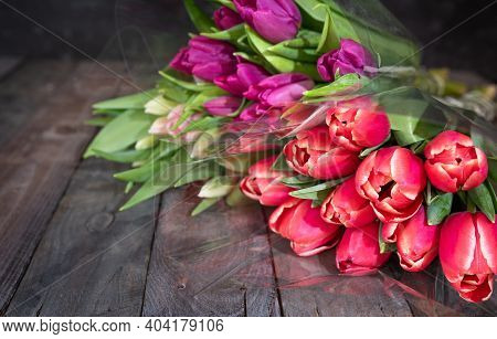 Bunch Of Fresh Red And Purple Tulips On Wooden Vintage Planks In Front Of Gray Concrete Wall. Spring