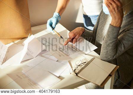 Senior Woman And Her Caretaker Scrutinizing Utility Bills