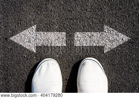 Choice Of Solutions, Paths, Strategies. Sneakers And Arrows In Different Directions On Asphalt. The