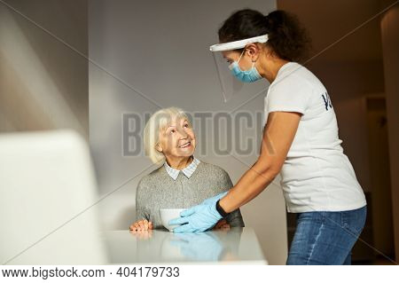 Caregiver Serving Breakfast To A Happy Senior Lady