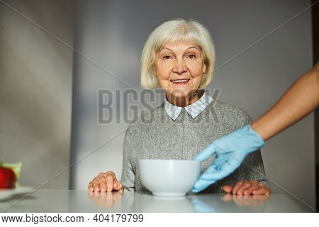 Smiling Female Pensioner Anticipating Her Morning Meal
