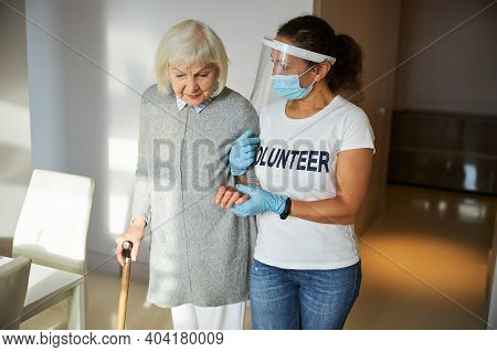 Carer In Latex Gloves Assisting A Pensioner To Walk