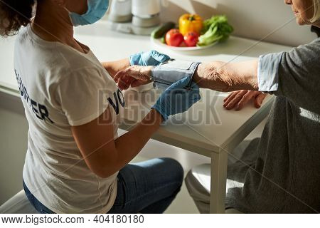 Caregiver Measuring The Senior Woman Blood Tension