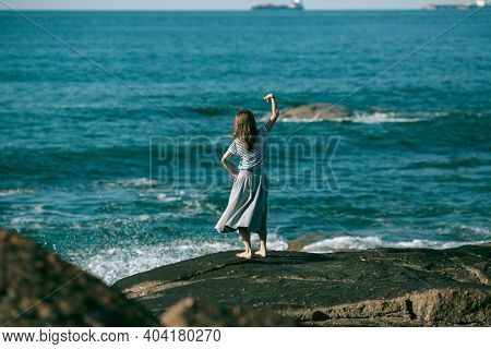Young dancers woman is engaged in choreography on the rocky coast of Atlantic ocean.
