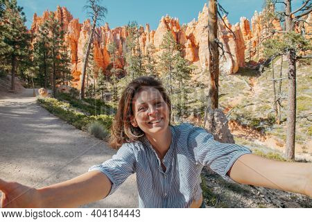 Happy Girl Takes Pictures And Takes A Selfie On The Background Of A Mountain Landscape. Young Woman