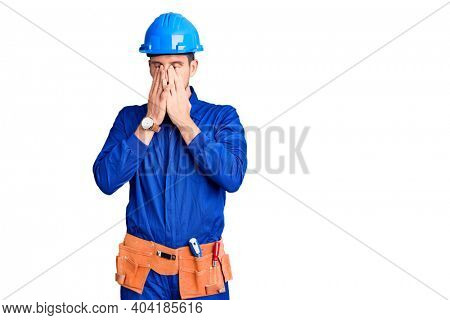 Young handsome man wearing worker uniform and hardhat pointing unhappy to pimple on forehead, ugly infection of blackhead. acne and skin problem