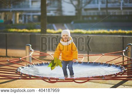 Adorable Toddler Girl In Yellow Jacket Having Fun On A Trampoline On A Fall Or Spring Day. Little Ki