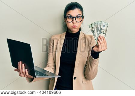 Young hispanic woman wearing business style holding laptop and 50 euros puffing cheeks with funny face. mouth inflated with air, catching air.