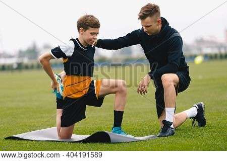 Soccer Coach With Young Player. Boy On Football Field Stretching On Exercise Mat. Male Coach And Per