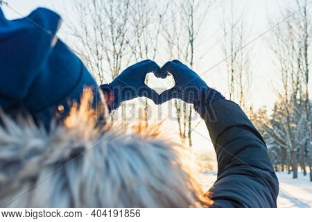 Woman Making Heart Symbol With Hands Wearing Gloves, Sunny Winter Evening, Sunrays, Valentines Day,
