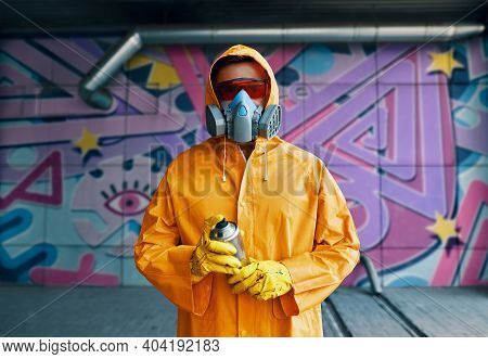 Graffiti Painter In Respirator Mask Standing Near The Wall With His Paintings Looking To Camera. Str