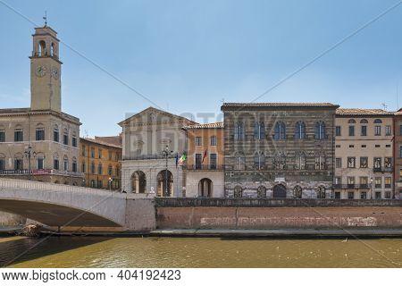 Pisa, Italy - March 31 2019: The Palazzo Pretorio And Its Clock Tower In Front Of The Ponte Di Mezzo