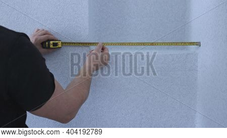 Taking Measurements Of A Niche From A Wall Covered With Gray Textured Wallpaper By A Man In A Black