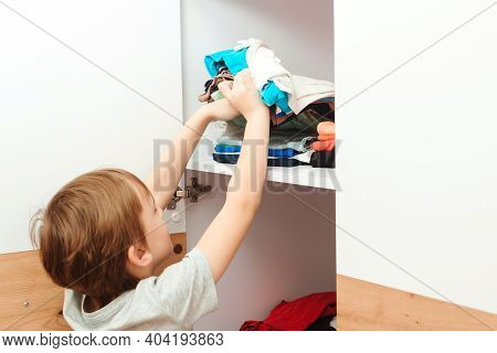 The Boy Puts Things In Order In The Closet. Kid Organizing Clothes In Wardrobe. Order In The Closet.