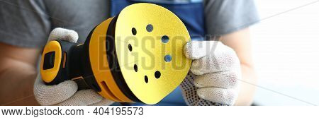 A Construction Tool For Polishing And Grinding Wood Surfaces. A Man In Gloves Holds A Spare Sole For