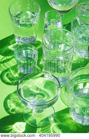 Water Glasses On A Green Background, Trendy Light And Shadow