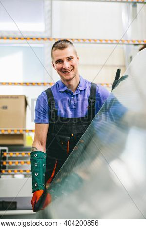 Glazier worker portrait with glass in workshop. Industry and manufactory production