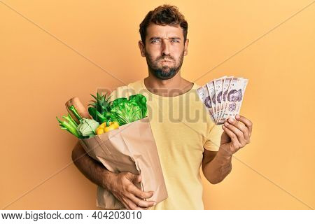 Handsome man with beard holding groceries and 500 mexican pesos banknotes puffing cheeks with funny face. mouth inflated with air, catching air.