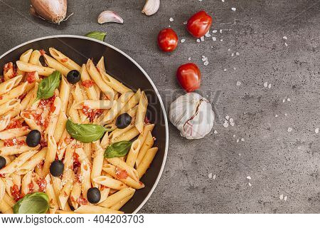 Pasta Penne With Tomato Bolognese Sauce, Parmesan Cheese, Olives And Basil.