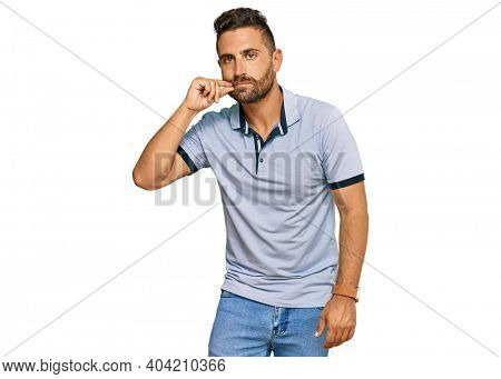 Handsome man with beard wearing casual clothes mouth and lips shut as zip with fingers. secret and silent, taboo talking