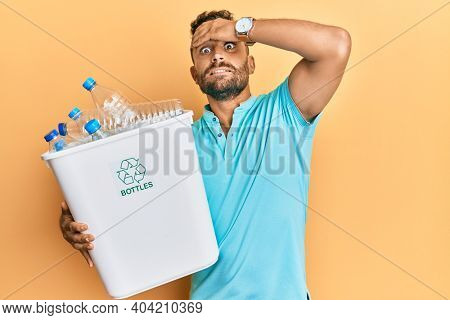 Handsome man with beard holding recycling wastebasket with plastic bottles stressed and frustrated with hand on head, surprised and angry face
