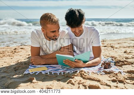 Young gay couple reading book lying on the sand at the beach.