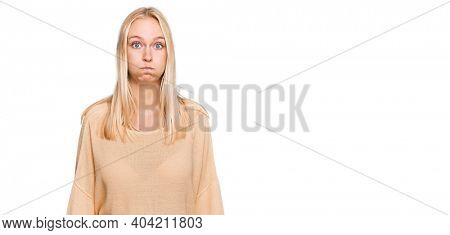 Young blonde girl wearing casual clothes puffing cheeks with funny face. mouth inflated with air, crazy expression.