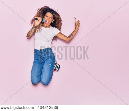 Young beautiful curly singer woman with tattoo smiling happy. Jumping with smile on face singing song using microphone doing rocker sign with fingers over isolated pink background