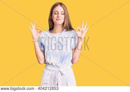 Young beautiful blonde woman wearing tye die tshirt relax and smiling with eyes closed doing meditation gesture with fingers. yoga concept.