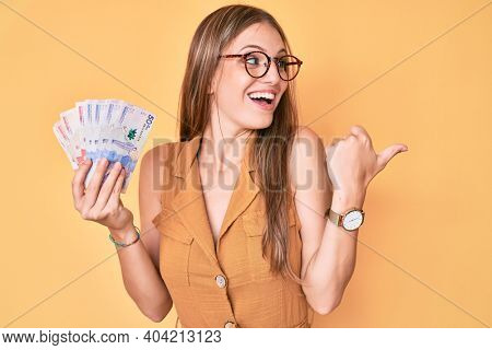 Young blonde girl holding colombian pesos pointing thumb up to the side smiling happy with open mouth