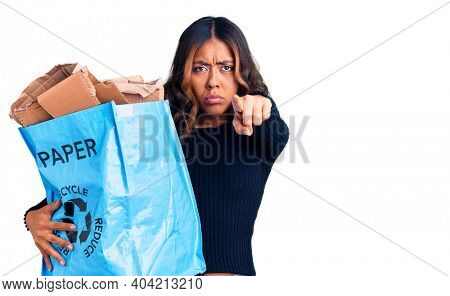 Young beautiful mixed race woman holding recycling wastebasket with paper and cardboard pointing with finger to the camera and to you, confident gesture looking serious