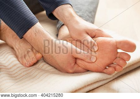 man doing flatfoot correction self massage at home