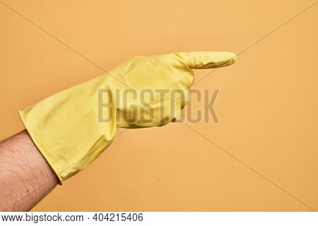 Hand of caucasian young man with cleaning glove over isolated yellow background pointing with index finger to the side, suggesting and selecting a choice