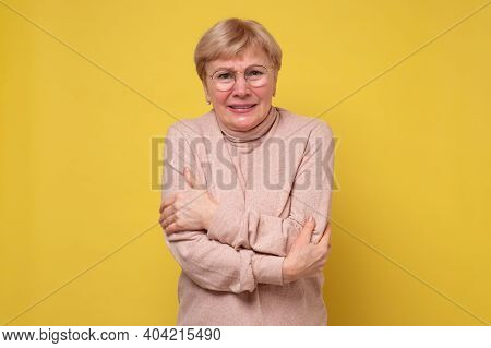 Mature Caucasian Trembling Woman, Isolated On Yellow Wall.