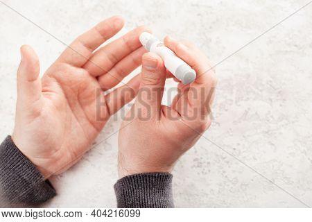 man hands using lancet on finger to check blood sugar or ketones level by glucose meter. medicine diabetes keto diet health care at home