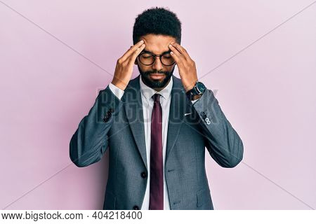 Handsome hispanic business man with beard wearing business suit and tie with hand on head for pain in head because stress. suffering migraine.