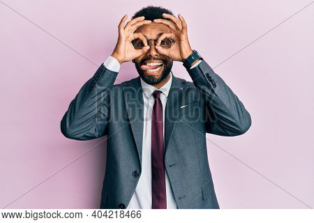 Handsome hispanic business man with beard wearing business suit and tie doing ok gesture like binoculars sticking tongue out, eyes looking through fingers. crazy expression.