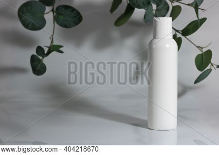 Skincare Cosmetic Bottle On White Gray Background, With A Green Plant. Spring Season Cosmetics. Dail