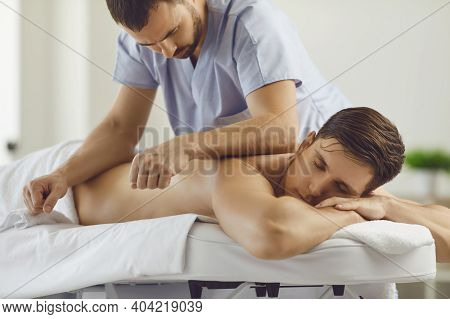 Relaxed Young Man Enjoying Remedial Body Massage In Spa Salon Or Wellness Center